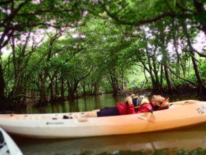 冬の西表島でカヌーに横たわる。